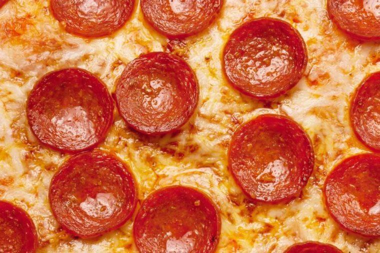 Pizza background - macro shot of pepperoni pizza