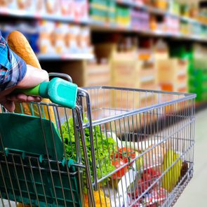 unhealthiest foods at the grocery store | Man pushing shopping cart full of food in the supermarket aisle. Elevated rear view. horizontal composition
