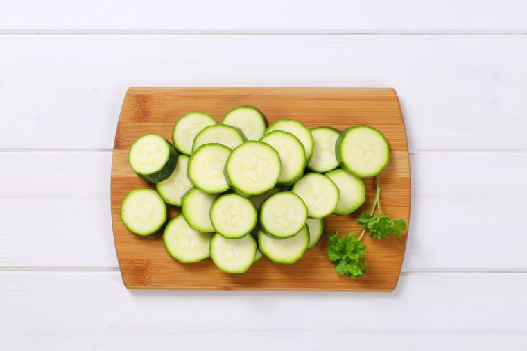 pile of green zucchini slices on wooden cutting board