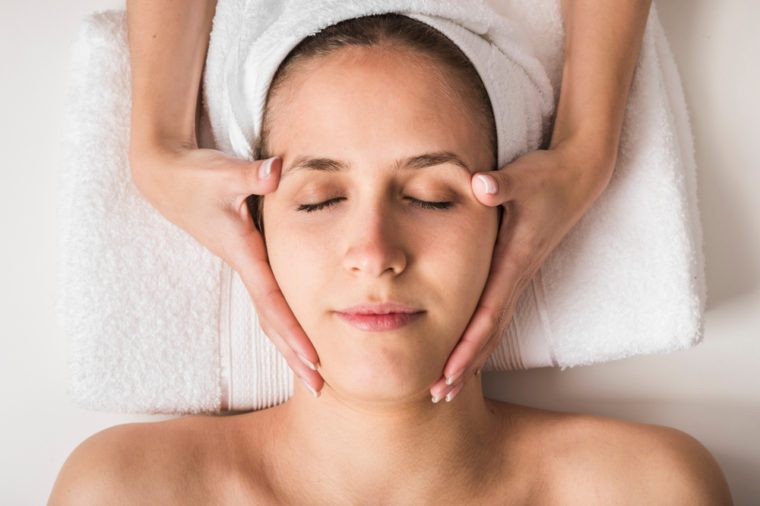 Anti-Aging Treatments | Spa concept. Face massage. Young woman getting spa treatment, close up