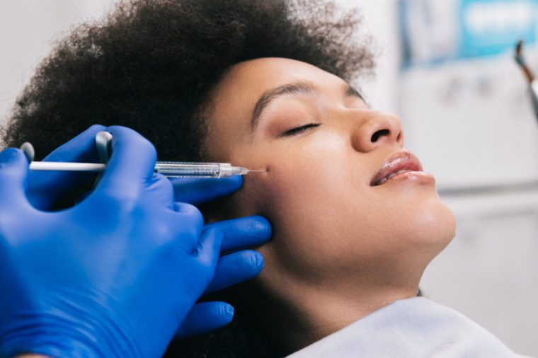 Anti-Aging Treatments | Attractive young African woman is getting a rejuvenating facial injections. She is sitting calmly at clinic. The expert beautician is filling female wrinkles by hyaluronic acid.