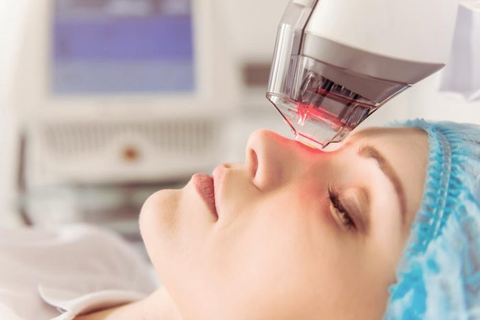 Anti-Aging Treatments | Beautiful female patient is getting a face skin treatment while lying at cosmeticians office, close up