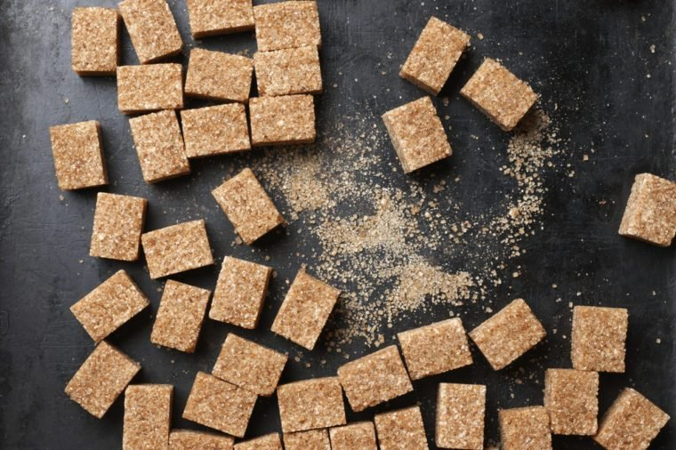 Natural brown sugar cubes on rough black background. Top view point.