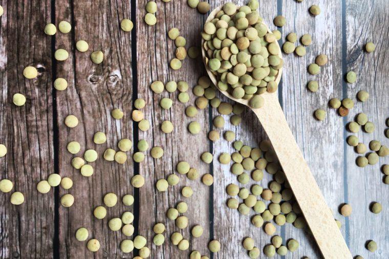Wooden spoon with lentils. Lentils. Concept lentils.