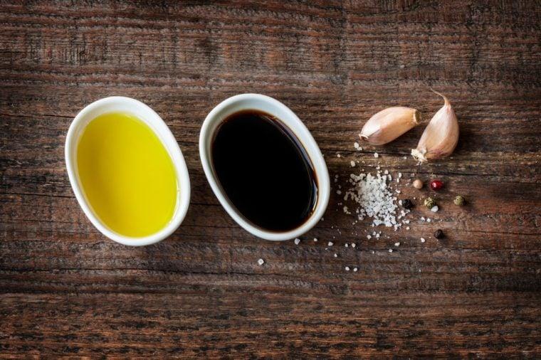 Vinaigrette or french dressing recipe ingredients on vintage wood background. Olive oil, balsamic vinegar, garlic, salt and pepper from above.