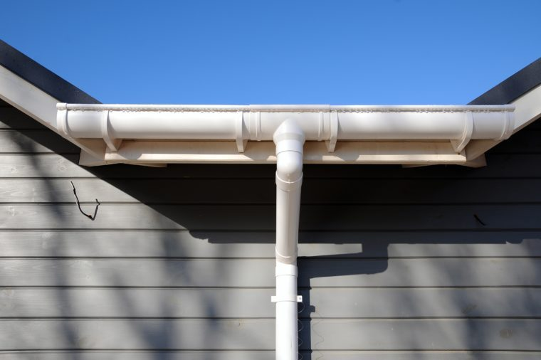 New rain gutter on a home against blue sky.
