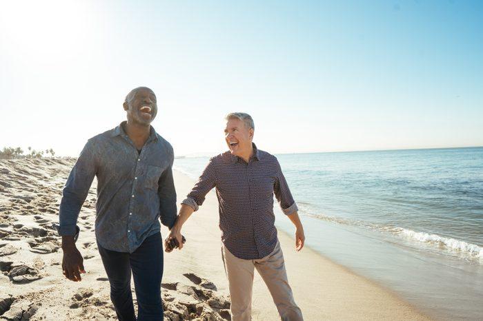 senior same sex couple holding hands on the beach