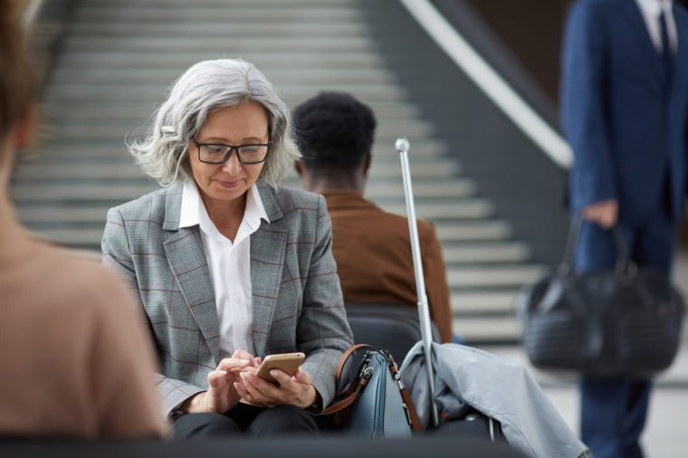older woman traveling in airport looking at her phone