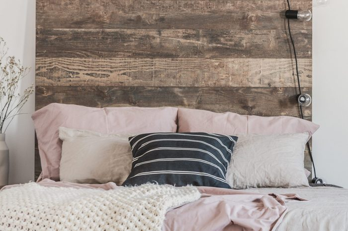 Cute ducks on grey oil painting in white rustic bedroom interior with fancy bookshelf and bed with wooden headboard