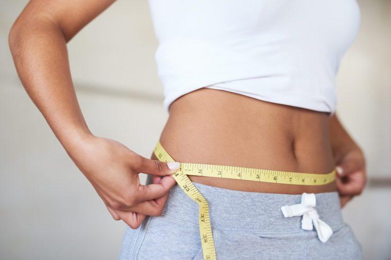 Gluten-free Diet | Celiac Disease | Gluten sensitivity | Gluten Intolerance | Woman measuring her waist in the bathroom