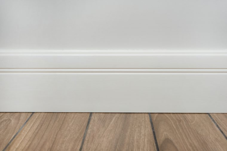 Light matte wall, white baseboard and tiles immitating hardwood flooring