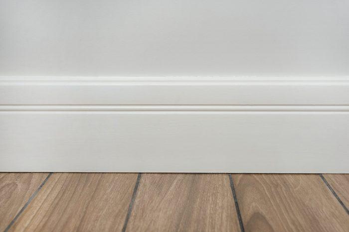 Light matte wall, white baseboard and tiles immitating hardwood flooring