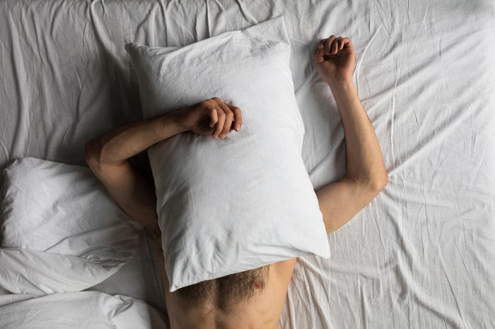 Wake up in the middle of the night | top view of shirtless man hiding face with pillow while sleeping in bed