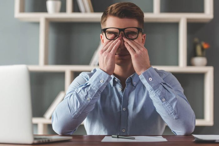 Attractive tired young businessman in eyeglasses is rubbing his eyes while working in office