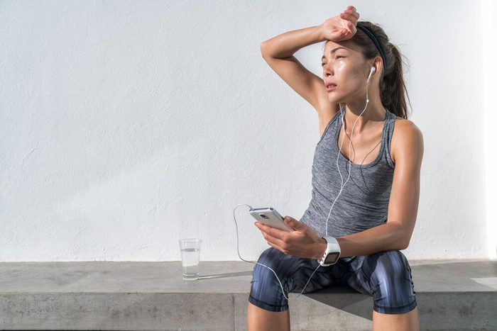 Tired fitness woman sweating taking a break listening to music on phone after difficult training. Exhausted Asian runner dehydrated feeling exhaustion and dehydration from working out at gym.