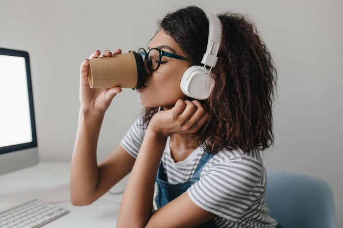 Elegant black girl with curly hairstyle drinking coffee at workplace posing near gray wall. Portrait of tired young woman in white headphones enjoying coffee beside computer.