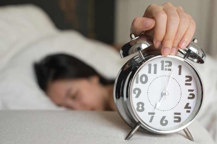 Young woman turns off the alarm clock waking up in the morning.