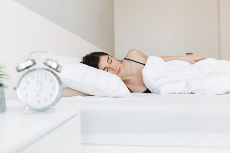 Portrait of a beautiful young woman sleeping in bed at the bedroom with alarm clock on a nightstand