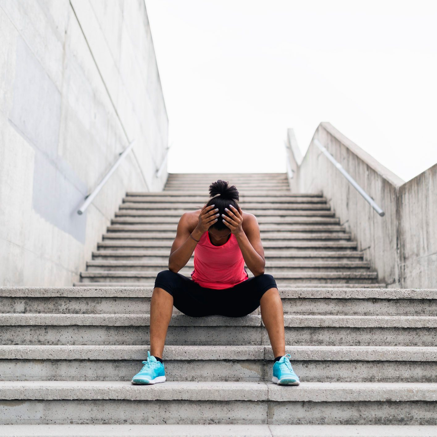 young woman sitting on stairs taking a break from workout
