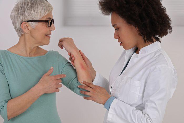 dermatologist looking at patient's sensitive skin