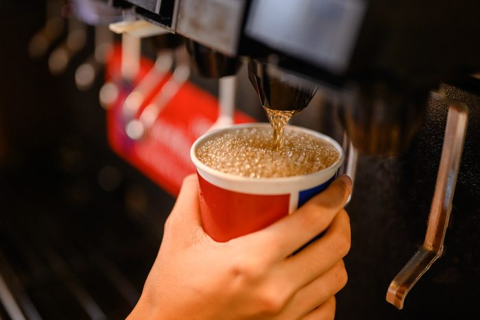close up of person filling up cup at soda fountain