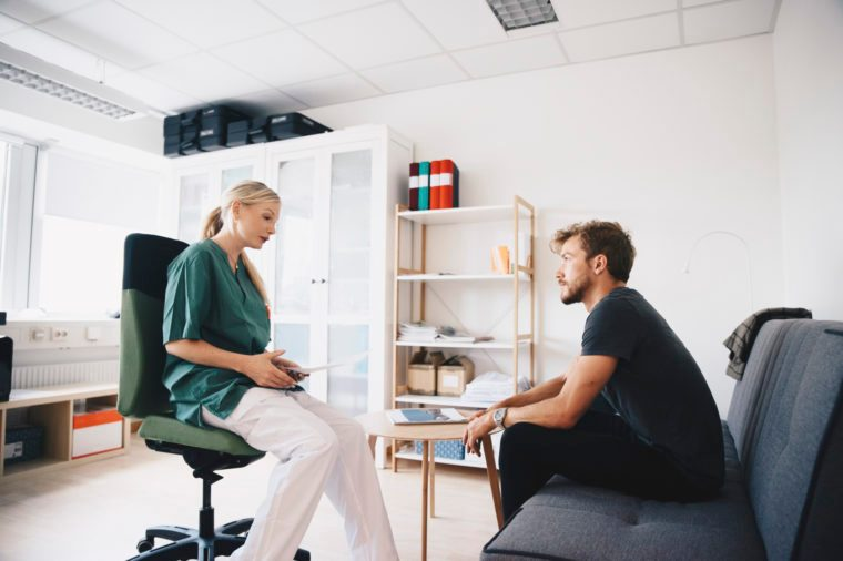 young man talking to female nurse at doctor's office
