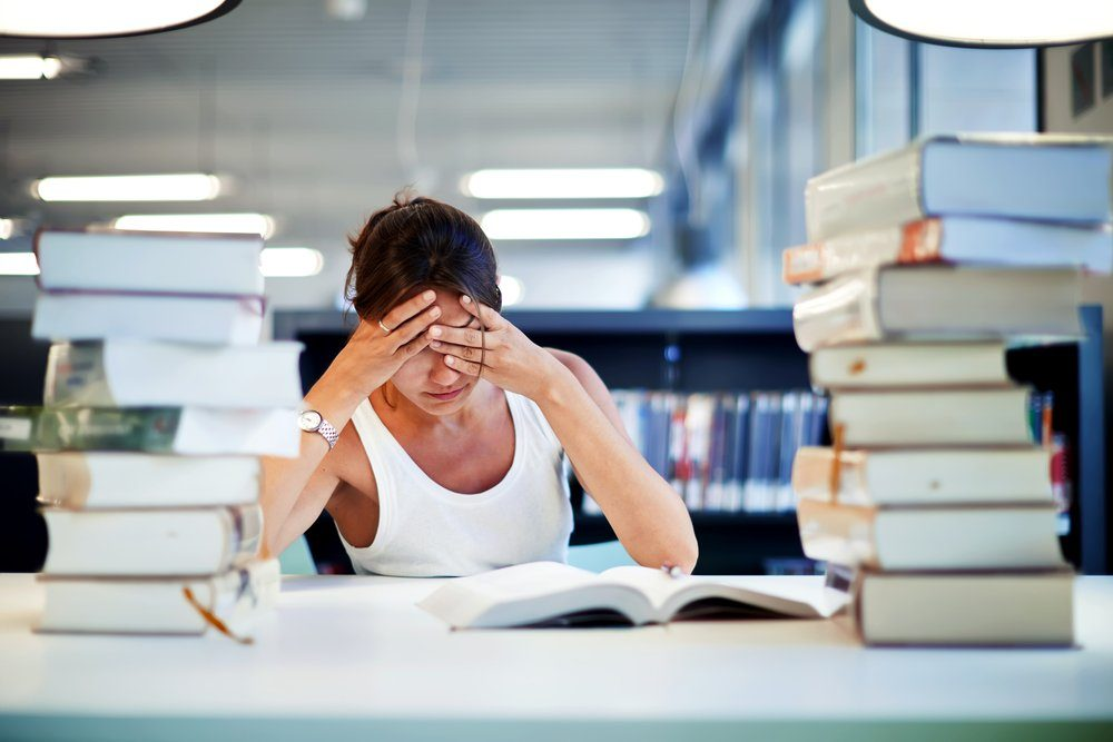frustrated woman in library with stack of books