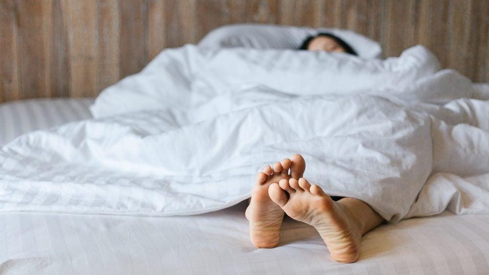early-onset Alzheimer's | Female feet under blanket flat lay. Female beautiful feet on the bed. Sleeping woman legs under white blanket