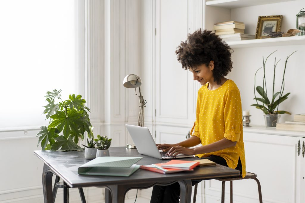 work from home | woman sitting at desk in home working on laptop
