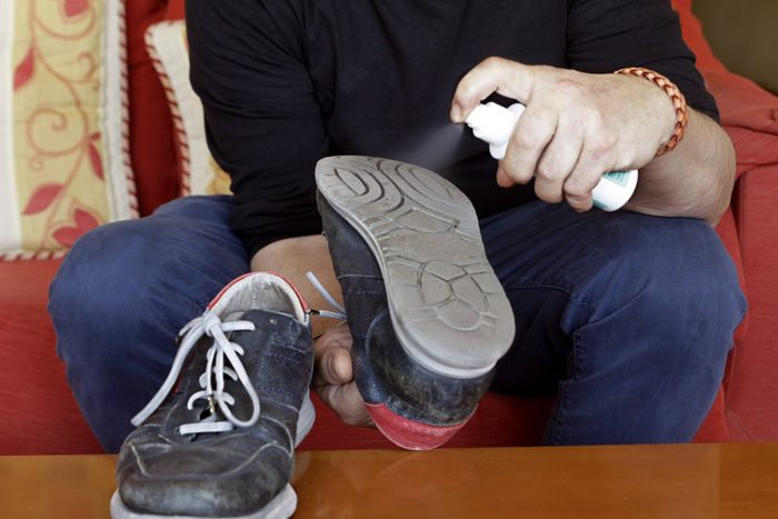 man disinfecting shoes to protect against coronavirus