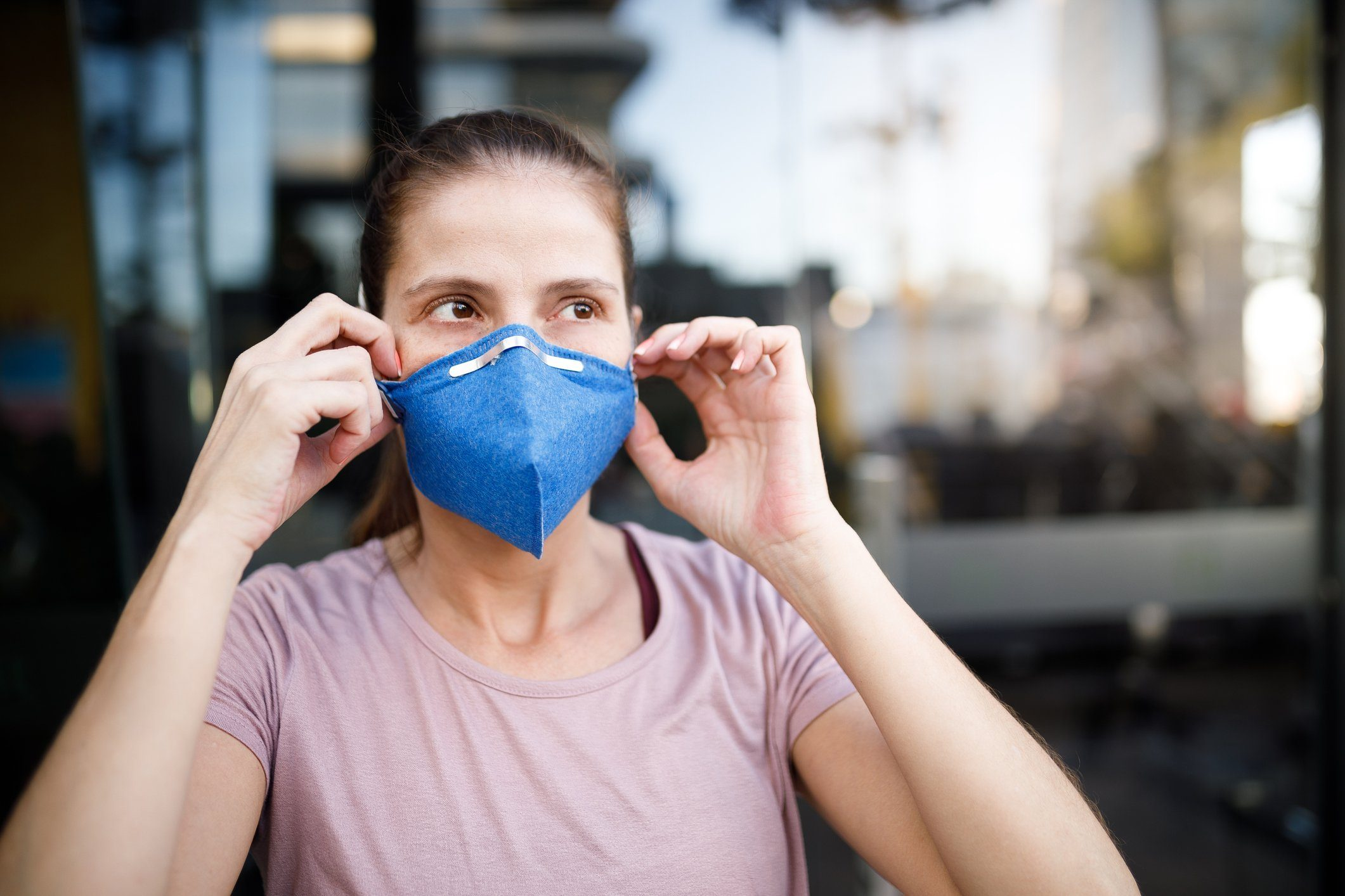 woman putting mask on face to protect from coronavirus