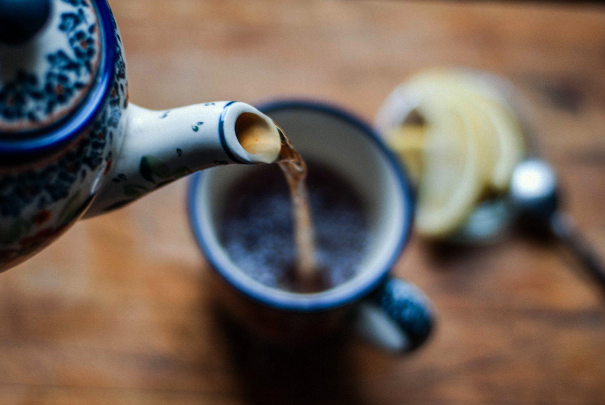 close up of tea kettle pouring tea into tea cup