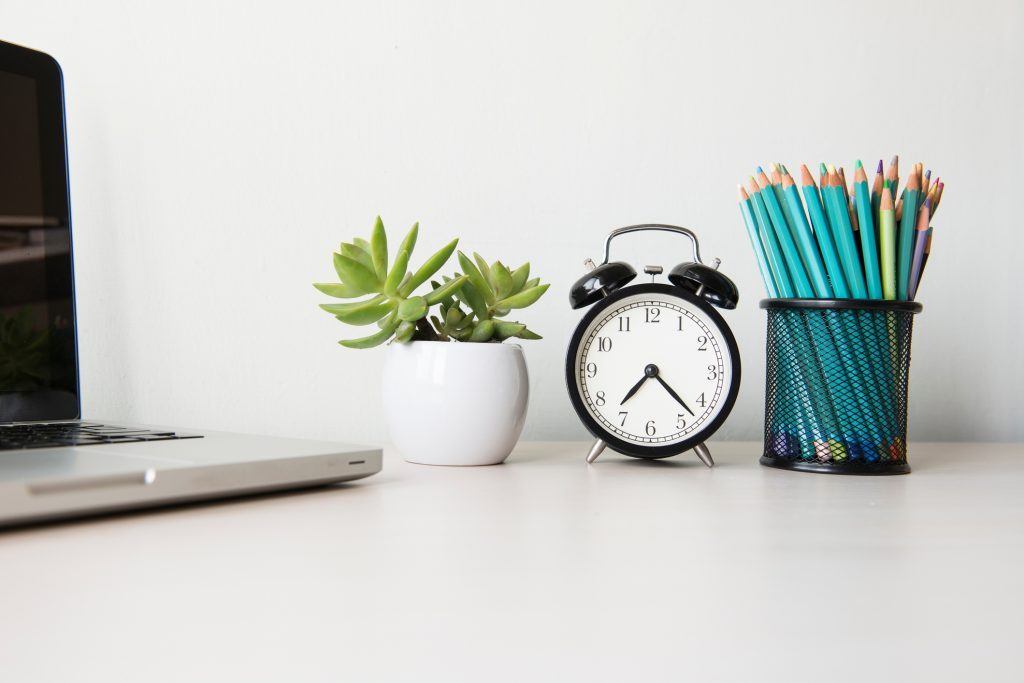 work from home | desk with laptop clock plant and pencils