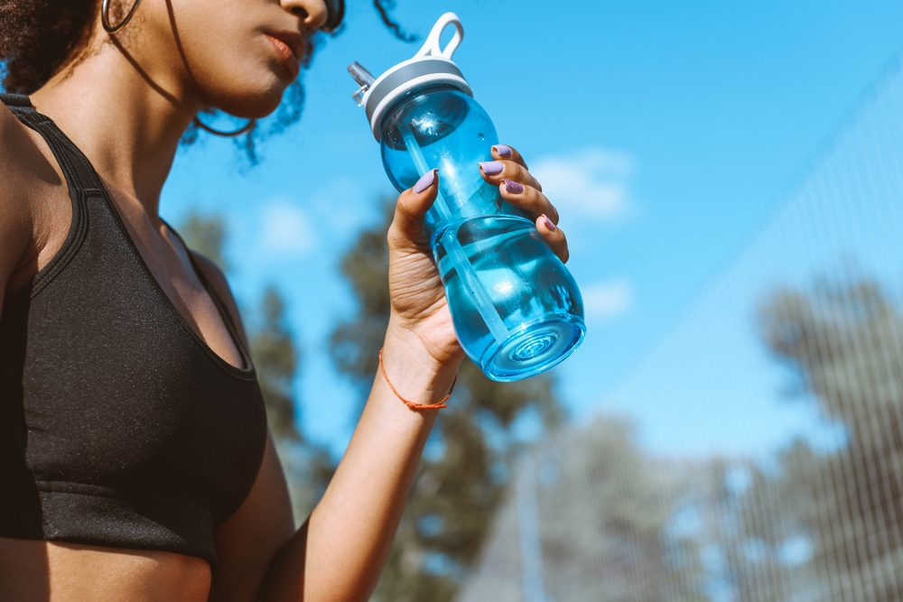health advice | Cropped shot of woman in sports bra drinking from blue water bottle