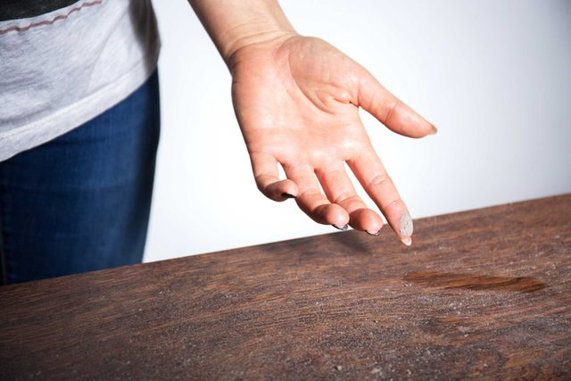 dust and hand on table