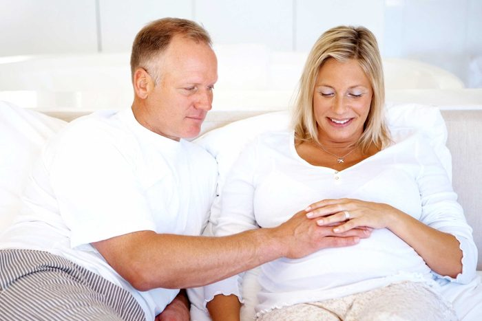 health myths gynecologists hear | man with hand on pregnant woman's belly