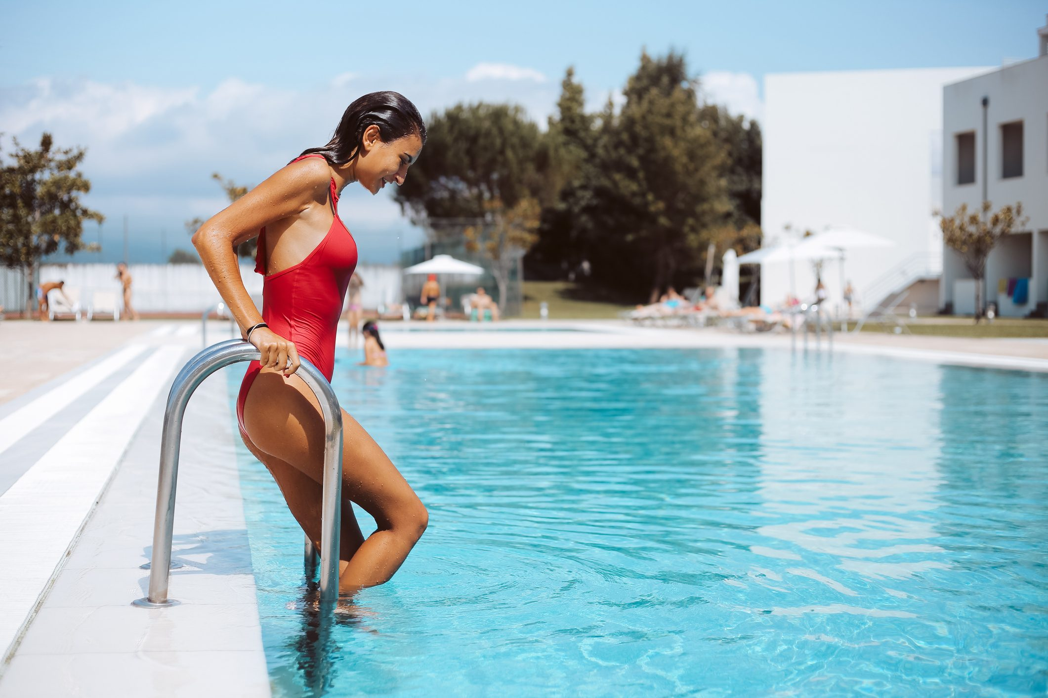 woman getting into swimming pool from ladder| catch coronavirus from swimming