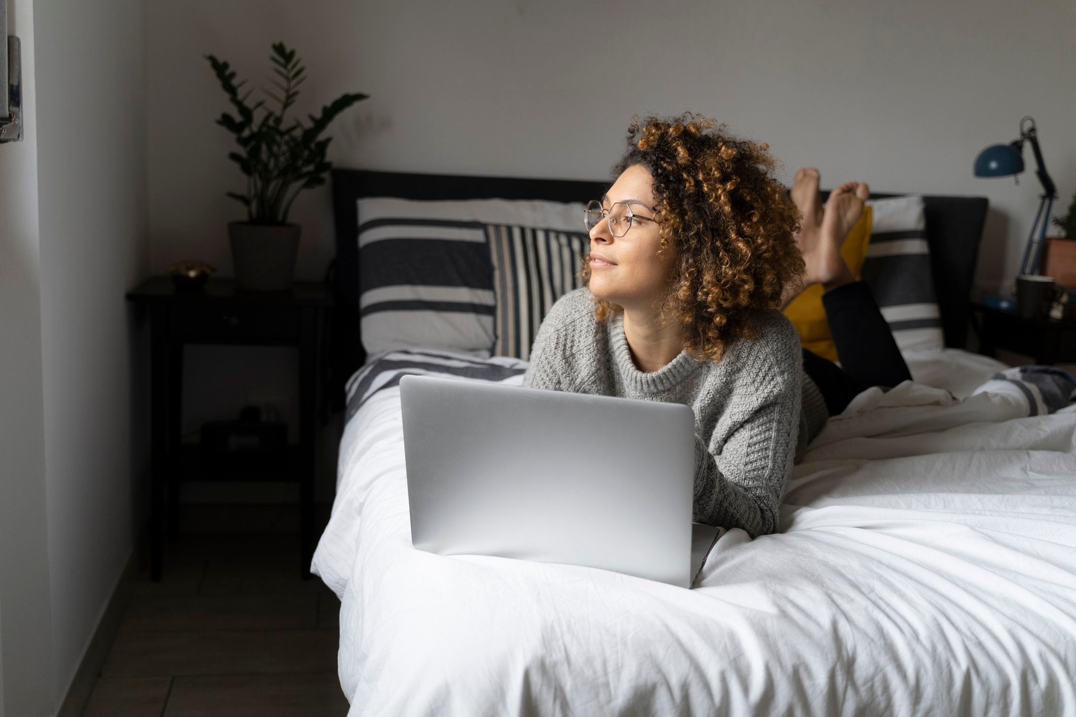 woman laying in bed with laptop