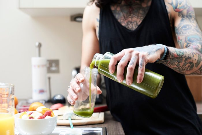 man pouring green juice into glass