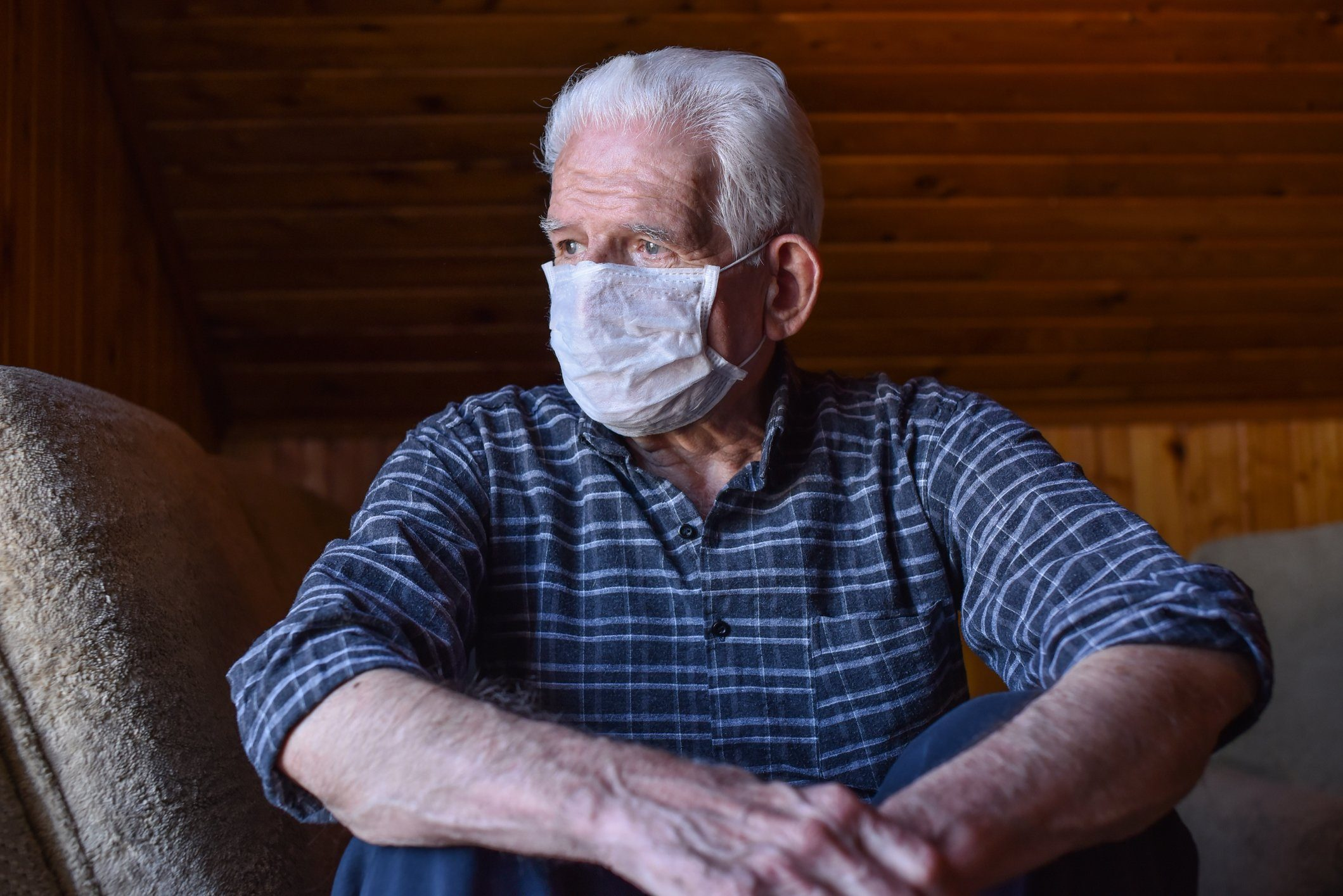 2020   Portrait of senior man with respiratory mask looking outside from home window during quarantine