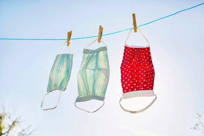 Still life of face masks hanging at clothesline against clear sky and sun, DIY sewing project