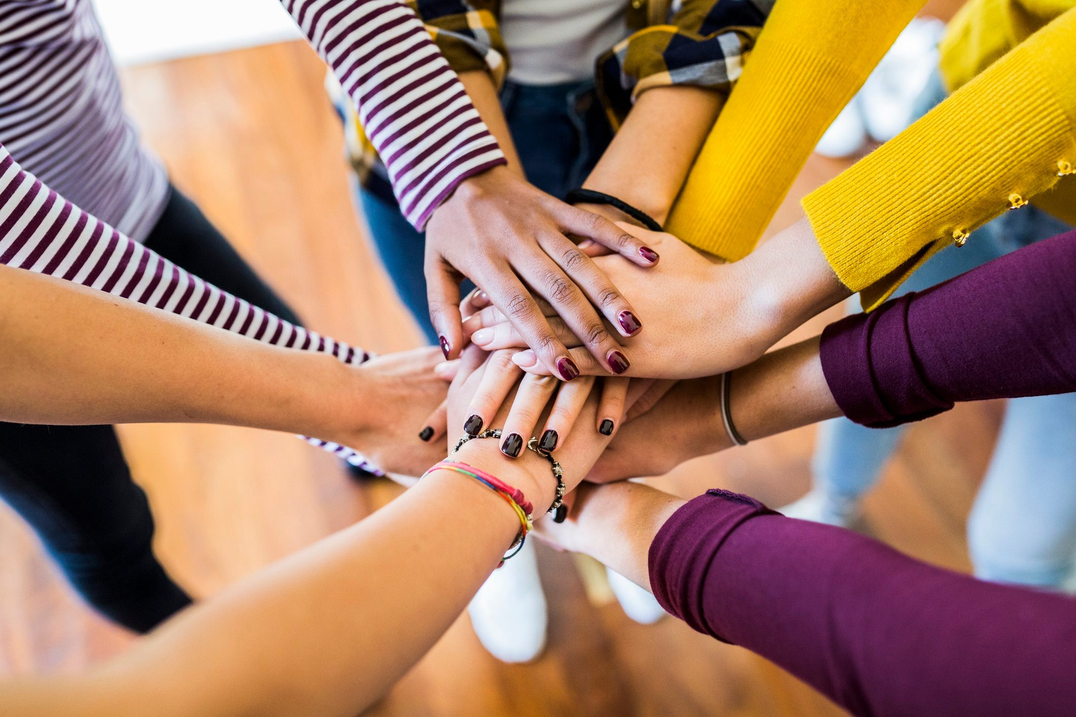 2020   Close-up of five women stacking their hands