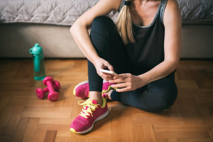 young woman looking at smartphone before workout