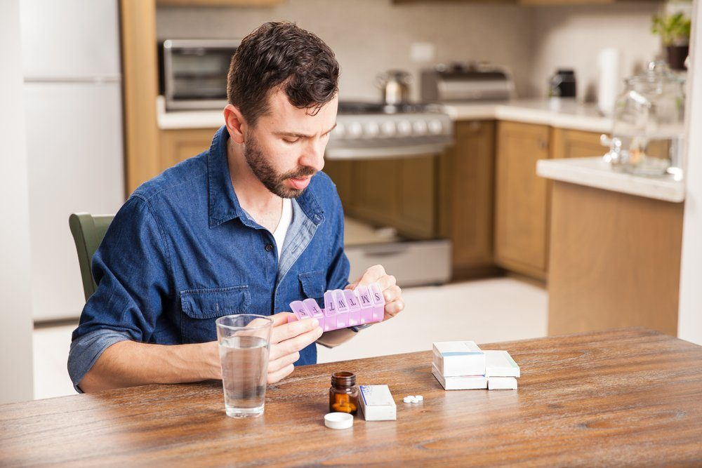 Young man with a beard sorting his medicines in a pill organizer at home