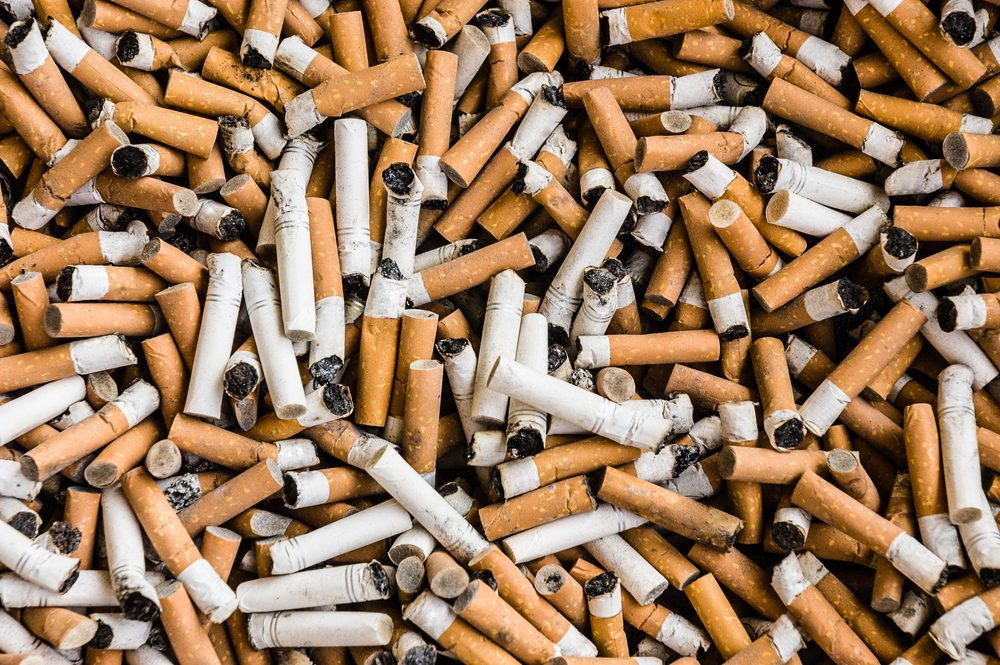 things that wreck your teeth | a lot of burnt cigarette butts with some ash