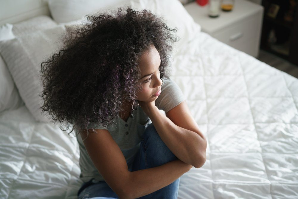 antidepressants | Lonely young latina woman sitting on bed. Depressed hispanic girl at home, looking away with sad expression.