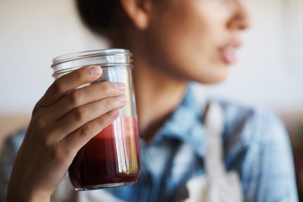 close up of woman holding healthy juice in glass