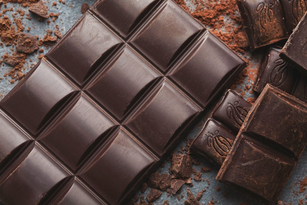 foods and drinks that cause migraines | Dark chocolate bar broken in pieces on dark background and cocoa powder closeup. Sweet wallpaper, confectionery shop advertising and cooking ingredients concept
