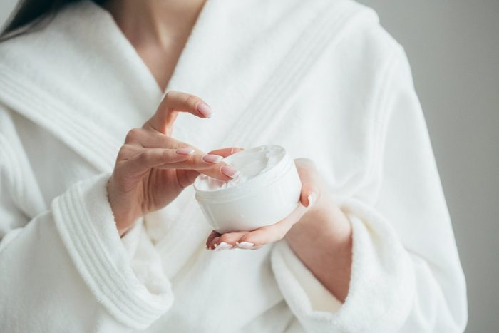 anti-aging advice | woman's hands holding a jar of beauty cream