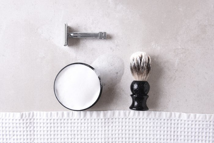 shouldn't be stored in the bathroom | Shaving Still Life: Safety razor with towel, brush and soap on a gray tile surface.